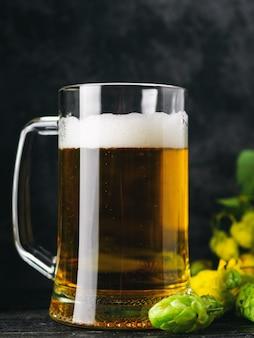 Beer mug on dark background with green hops