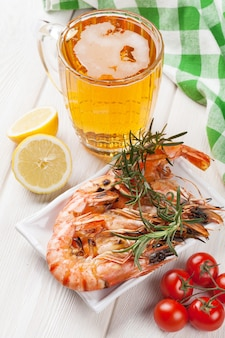 Beer mug and grilled shrimps on wooden table