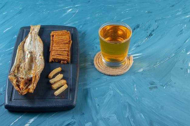 Пивная кружка рядом с сушеной рыбой и гренками на подносе, на синем фоне.