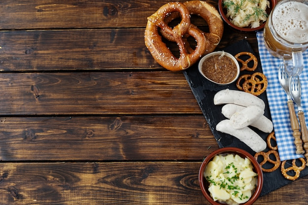 Beer mug, pretzels and sausages on wooden table background in top view