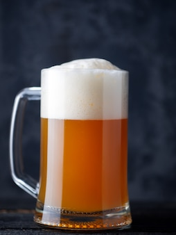 Beer mug unfiltered wheat beer close-up with a large foam cap