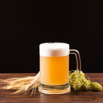 Beer mug with barley and hops on wooden board