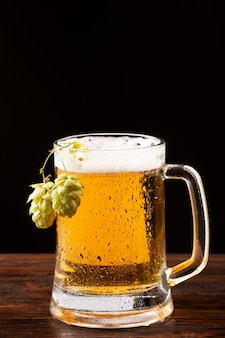 Beer mug with foam and hops on wooden board