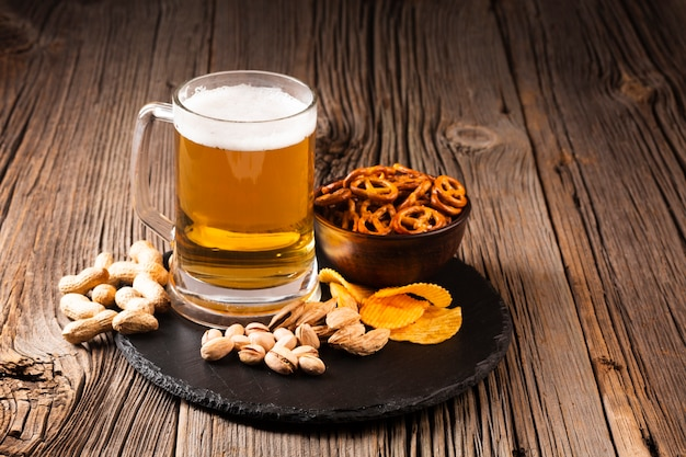 Beer mug with pistachio and snacks on wooden board