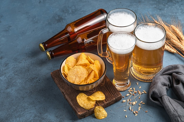 Beer mugs and bottles chips and wheat on a dark background horizontal view space for copying