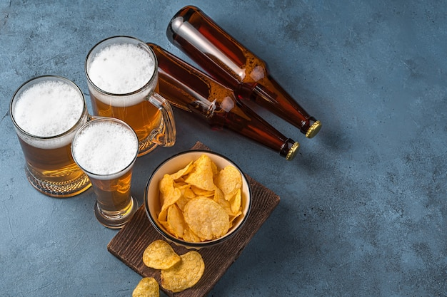 Beer mugs chips and beer bottles on a dark blue background horizontal view space for copying