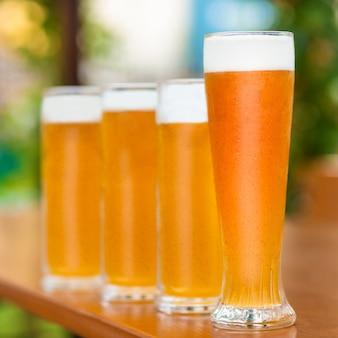 ビールジョッキ、緑の背景と並んでグラス