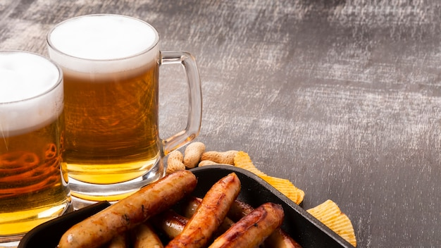 Beer mugs and sausages on dark background