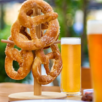 テーブル、緑の背景にプレッツェルのビールジョッキ