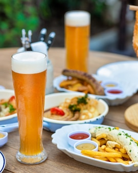 テーブルの上のソーセージ、肉料理、プレッツェル、ソースのビールジョッキ