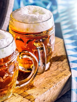 ビール。オクトーバーフェスト。2つの冷たいビール。生ビール。ドラフトエール。ゴールデンビール。ゴールデンエール。上に泡が付いた2つの金ビール。パブホテルやレストランのガラス瓶に冷たいビールをドラフトします。静物。