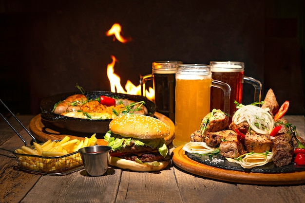 Beer party dinner table background with beer glasses and different food. hamburger, fried sausages, french fries and grilled meat on the table. fire flame on the backdrop.