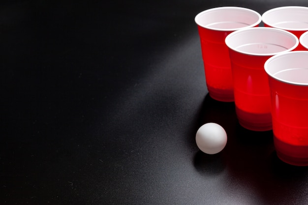 Beer pong college game on black background