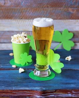 맥주, 성 패트릭 모자 모양의 종이컵에 담긴 팝콘, 나무 테이블에 토끼풀