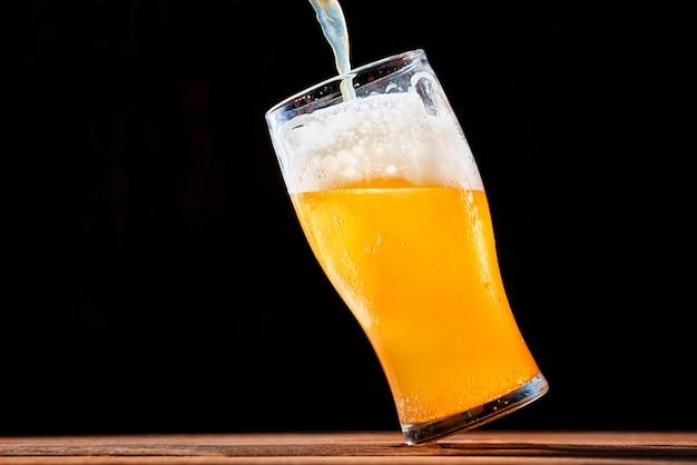 暗い背景にグラスに注ぐビール