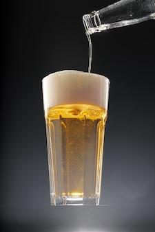 黒の背景にグラスに注ぐビール