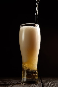 Beer pours into glass on black background