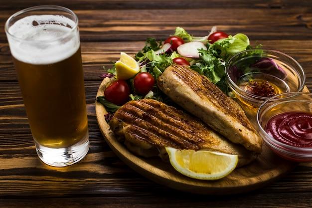 Birra e salsa vicino a pollo e insalata