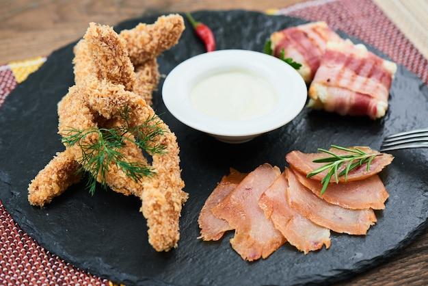 Пивная закуска, состоящая из куриных наггетсов, карпаччо и обратного бутерброда, подается на каменной доске