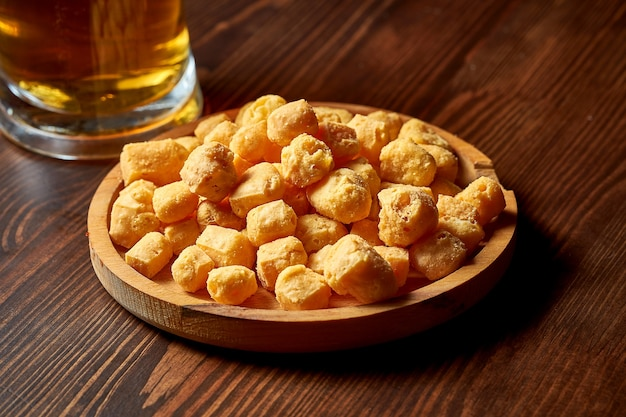Закуска к пиву - хрустящий сыр в деревянной тарелке