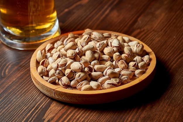 Закуска к пиву - жареные соленые фисташки в деревянной тарелке