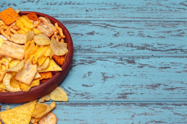 Beer snacks like crackers, chips, cookies on a wooden background