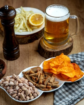 Beer snacks, a mug of beer, and a dish with lemon and string cheese