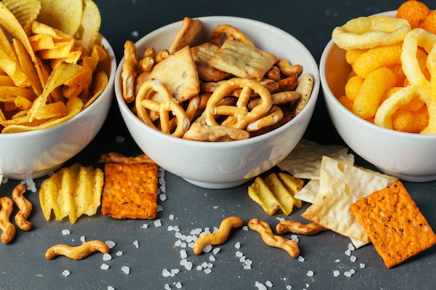 Beer snacks on stone table. various crackers, potato chips. top view