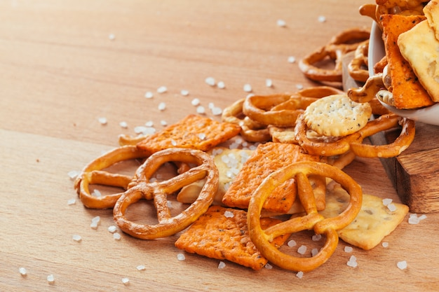Beer snacks on stone and wooden background