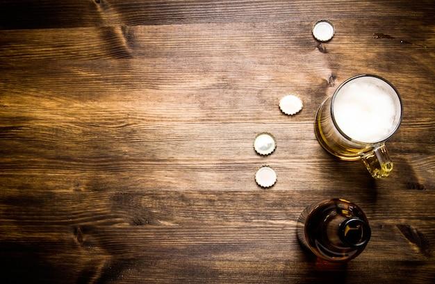 ビールスタイル-ボトル、グラスのビール、木製のテーブルのカバー