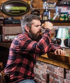 ビールの時間。男はバーカウンターでビールを飲みます。