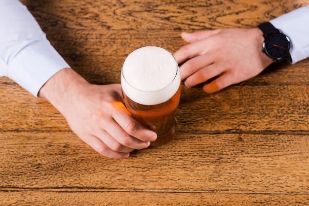 맥주 타임. 바 카운터에 맥주 잔을 들고 있는 남성 손의 상위 뷰