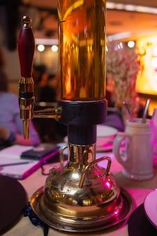 テーブルの上に5リットルのビールタワー。パブで大企業のためのビール。