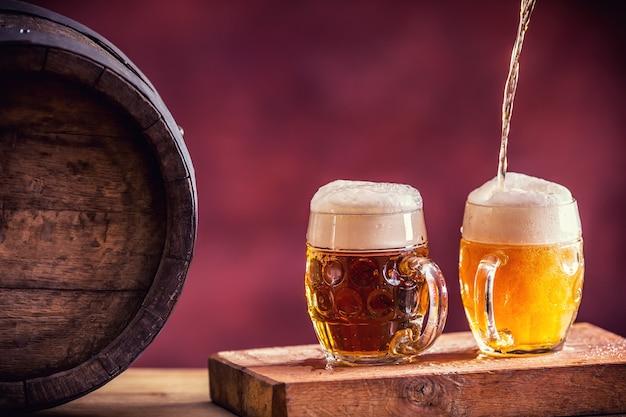 ビール。 2つの冷たいビール。生ビール。ドラフトエール。ゴールデンビール。ゴールデンエール。上に泡が付いた2つの金ビール。ホームパブホテルまたはレストランのガラス瓶に冷たいビールをドラフトします。静物。
