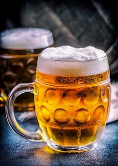 ビール。 2つの冷たいビール。生ビール。ドラフトエール。ゴールデンビール。ゴールデンエール。上に泡が付いた2つの金ビール。パブホテルやレストランのガラス瓶に冷たいビールをドラフトします。静物。