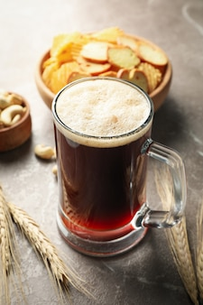 Пиво, пшеница и закуски на сером столе, крупным планом
