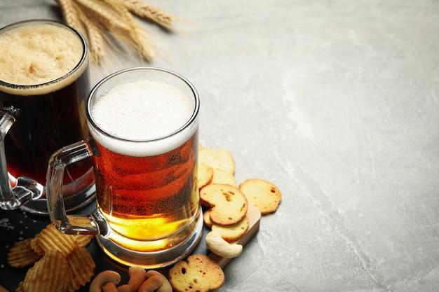 Пиво, пшеница и закуски на сером столе