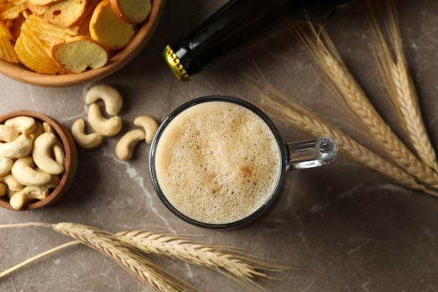 Пиво, пшеница и закуски на сером, вид сверху