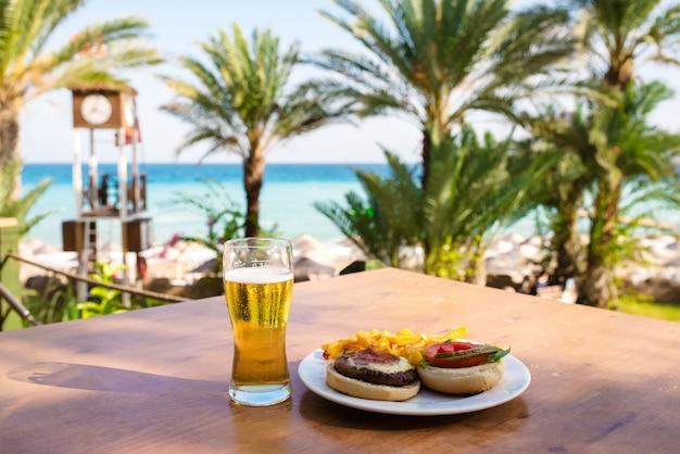 Пиво с бургером на фоне моря