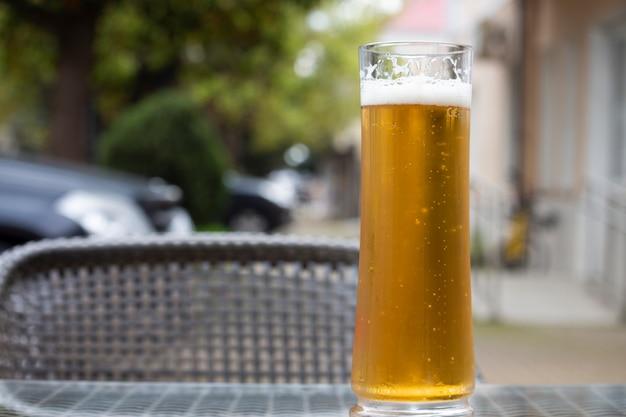 Пиво со стеклянной кружкой на столе на террасе летнего кафе. летние каникулы и алкоголь