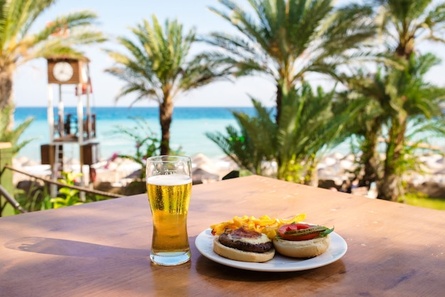 Beer with a burger against the background of the sea