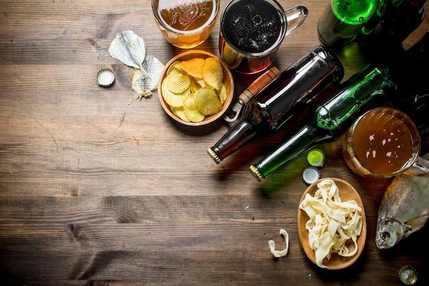 그릇과 말린 생선에 칩과 오징어 링이있는 맥주. 나무 테이블에