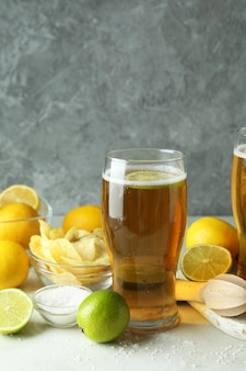 Beer with citrus against gray textured background