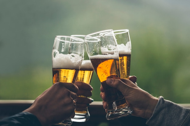 토스트 클로즈업을 올리는 친구의 손에 거품이 가벼운 키 큰 소년이 있는 맥주