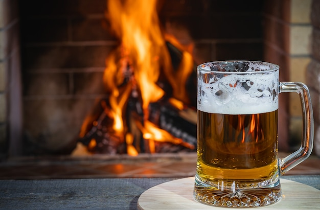 Beer with foam in the mug, on wooden table, against cozy fireplace