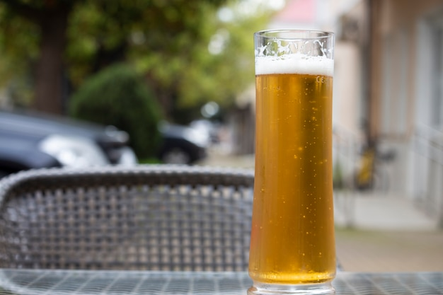 Beer with a glass mug on the table on the terrace of an outdoor cafe. summer holidays and alcohol