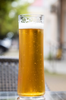 Beer with a glass mug on a wooden table on the terrace of an outdoor cafe. in the background is a car. summer holidays and alcohol
