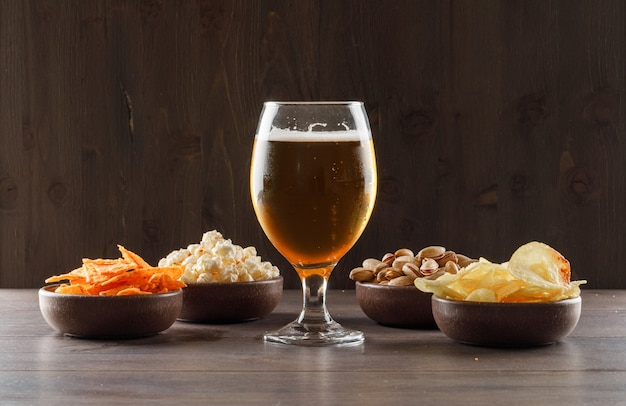 Beer with junk food in a goblet glass on wooden table, side view.
