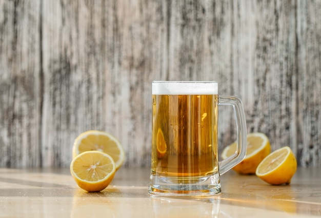 Beer with lemon slices in a glass mug on grungy and light table, side view.