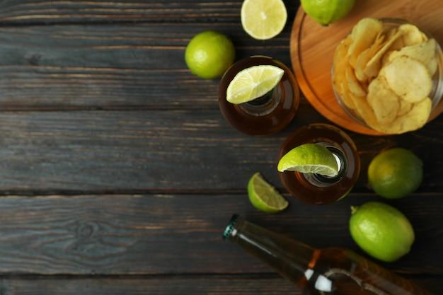 木製の背景にライムとチップのビール
